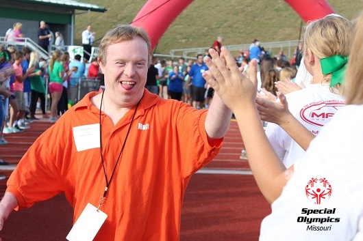 Special Olympics Missouri participant running through a finish line