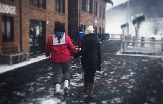Two girls walking into a ski lodge